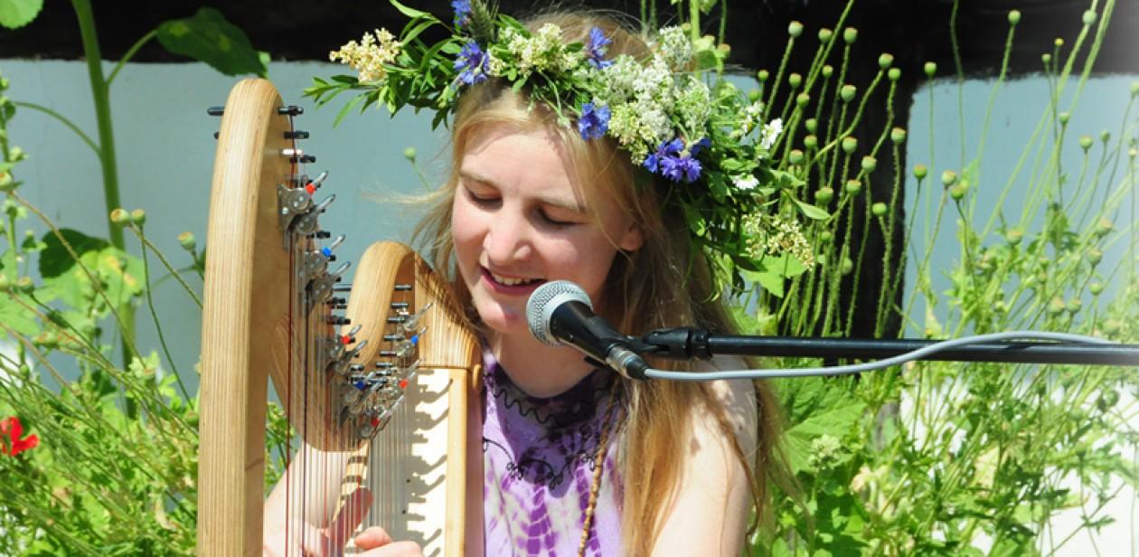 Na zdjęciu znajduje się kobieta grająca na harfie