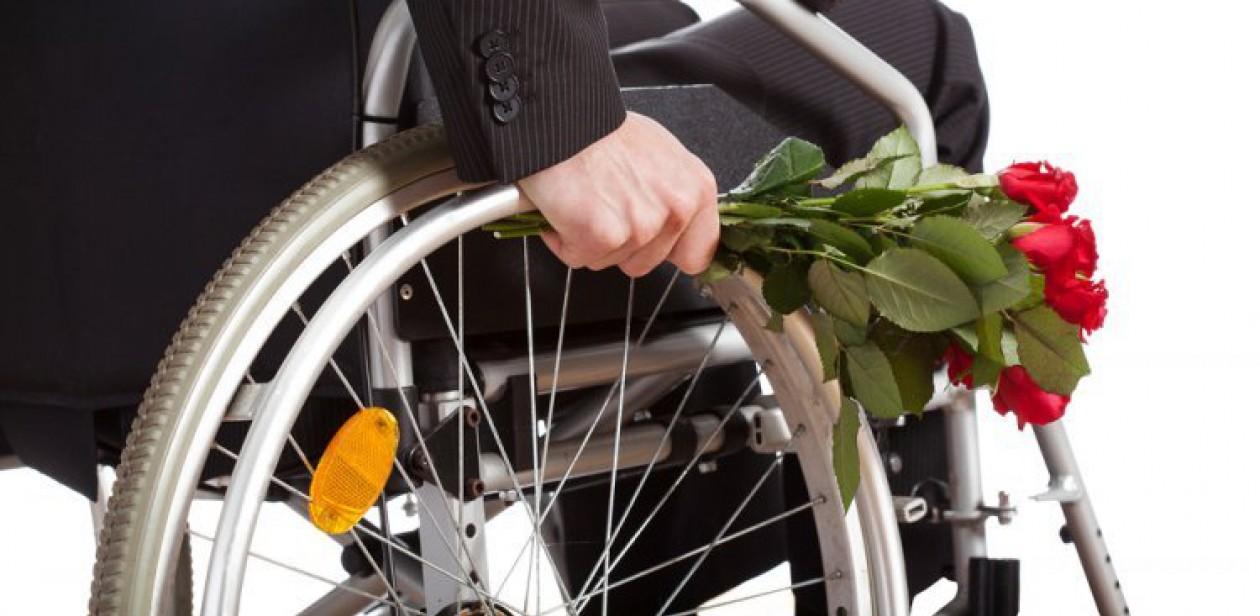 Na zdjęciu osoba na wózku inwalidzkim z bukietem róż
