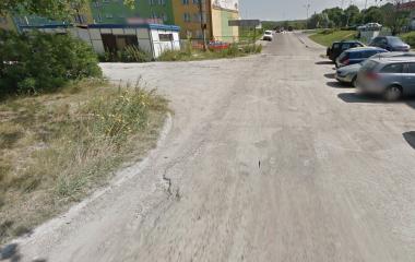 Zdjęcie drogi gruntowej. Po prawej stronie znajdują się zaparkowane samochody.