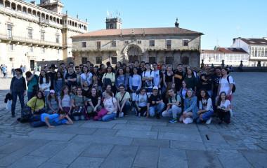 Zdjęcie grupy uczniów wraz z ich opiekunami. Znajdują się oni na placu w mieście Vigo w Hiszpanii. Jest słonecznie. Wszyscy są zadowoleni.