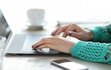 Na zdjęciu ukazane są dłonie piszące na klawiaturze laptopa