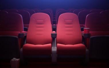 Zdjęcie przedstawia puste, czerwone fotele w sali kinowej