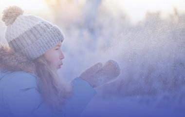 Dziewczynka w czapce bawiąca się śniegiem