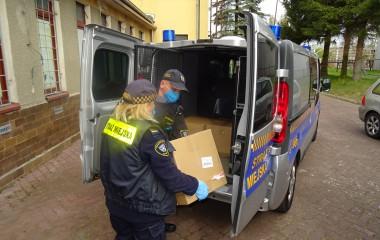 Dwoje Strażników Straży Miejskiej pakuje kartony z maseczkami ochronnymi do służbowego auta