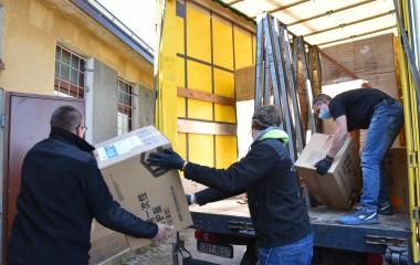 Na zdjęciu znajdują się ludzie pakujący kartony ze specjalnymi kombinezonami