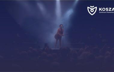 Na grafice znajduje się osoba na scenie śpiewająca do mikrofonu i grająca na gitarze