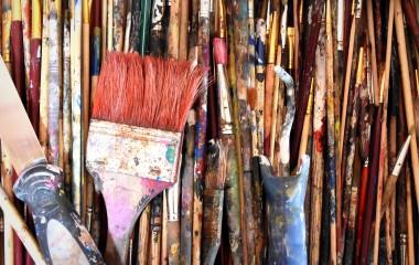 Obrazek przedstawia akcesoria malarskie w postaci pędzli pokrytych kolorową farbą