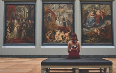Zdjęcie przedtawia kobietę wpatrującą w dzieła malarskie