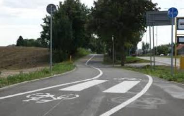 Fragment ścieżki rowerowej z przejściem dla pieszych oraz z przystankiem autobusowym z prawej strony, ciągnącej się dalej wzdłuż kłębistych ciemnozielonych drzew