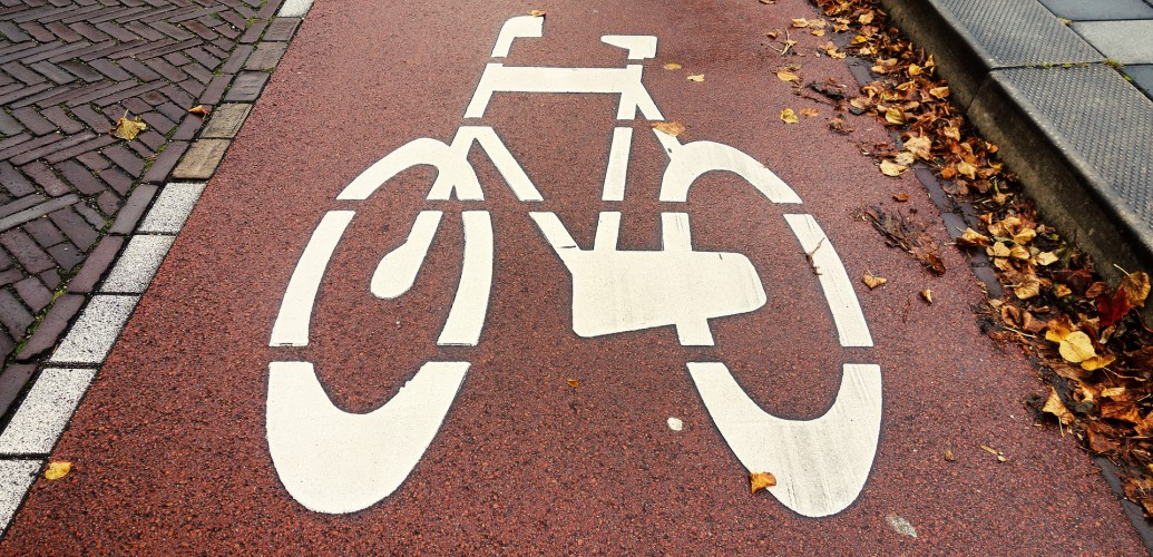 biały namalowany znak roweru na czerwonym gruncie
